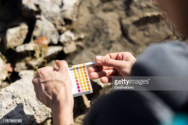 close-up of adult woman measuring ph value in nature - stock photo - alkaline stock pictures, royalty-free photos & images