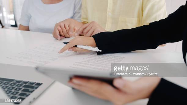 close-up of agent showing digital tablet to customers in office - life insurance stock pictures, royalty-free photos & images
