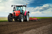 Close-up of agriculture red tractor cultivating field over blue sky