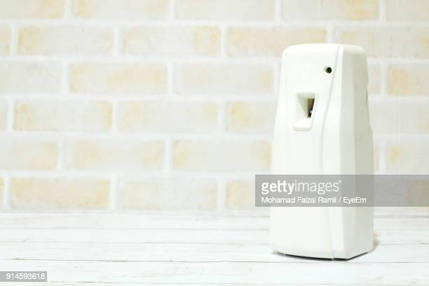 Close-Up Of Air Freshener On Table Against Wall