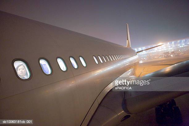Close-up of airplane at airport with faces at windows, night