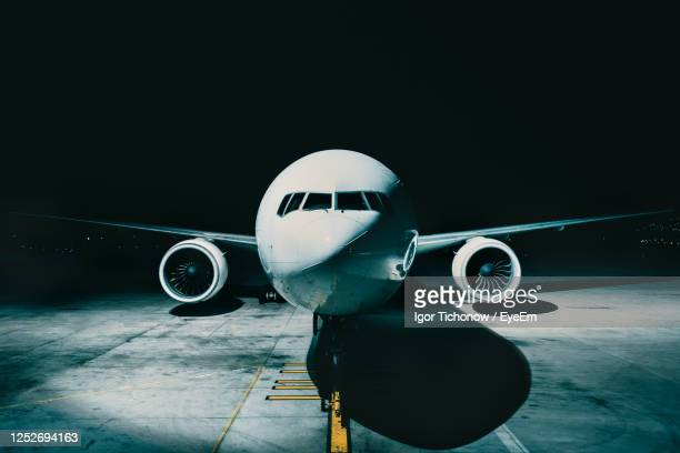 close-up of airplane on runway at night - air vehicle stock pictures, royalty-free photos & images