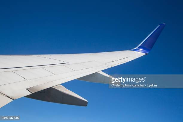 close-up of airplane wing against clear blue sky - aircraft wing stock pictures, royalty-free photos & images