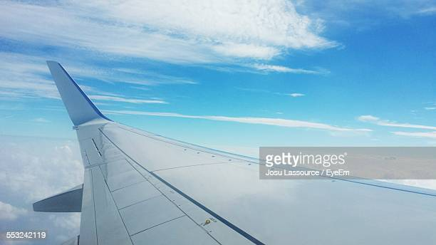 close-up of airplane wing flying above clouds - aircraft wing stock pictures, royalty-free photos & images