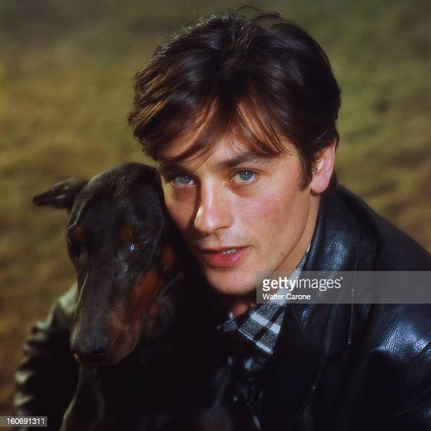 Closeup Of Alain Delon Plan de face souriant d'Alain DELON en veste de cuir noir serrant son chien contre lui