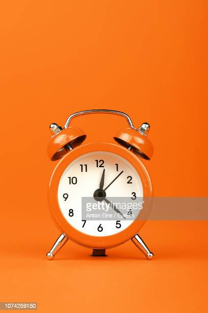 close-up of alarm clock against orange background - alarm clock stock pictures, royalty-free photos & images