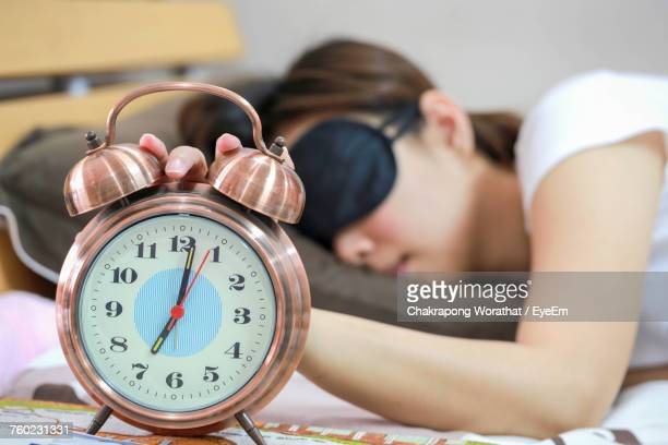 Close-Up Of Alarm Clock Against Woman Sleeping On Bed