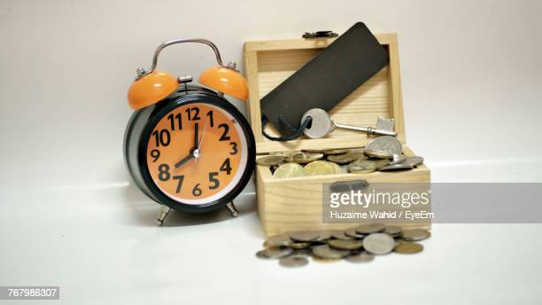 Close-Up Of Alarm Clock By Coins And Key In Box On White Table