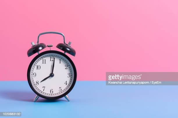 close-up of alarm clock on blue table against pink wall - temps qui passe photos et images de collection