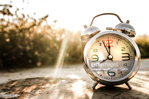 close-up of alarm clock on footpath - instrument of time stock pictures, royalty-free photos & images