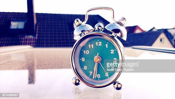 Close-Up Of Alarm Clock On Table Against Houses