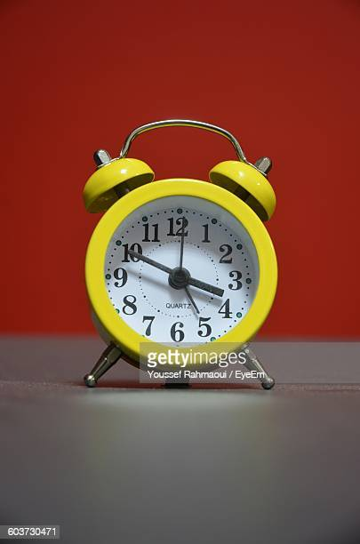 Close-Up Of Alarm Clock On Table Against Red Wall