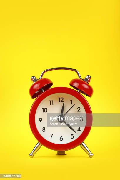 close-up of alarm clock on yellow background - alarm clock stock pictures, royalty-free photos & images