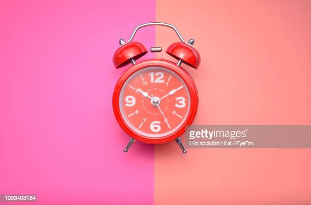 close-up of alarm clock over colored background - día fotografías e imágenes de stock