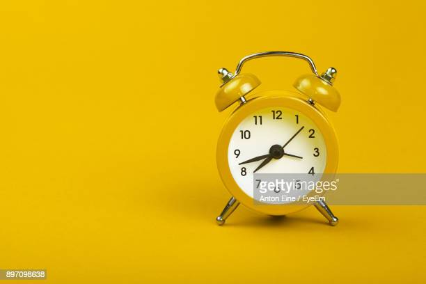 close-up of alarm clock over yellow background - día fotografías e imágenes de stock