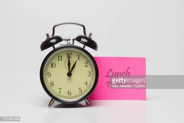 Close-Up Of Alarm Clock With Adhesive Note Against White Background
