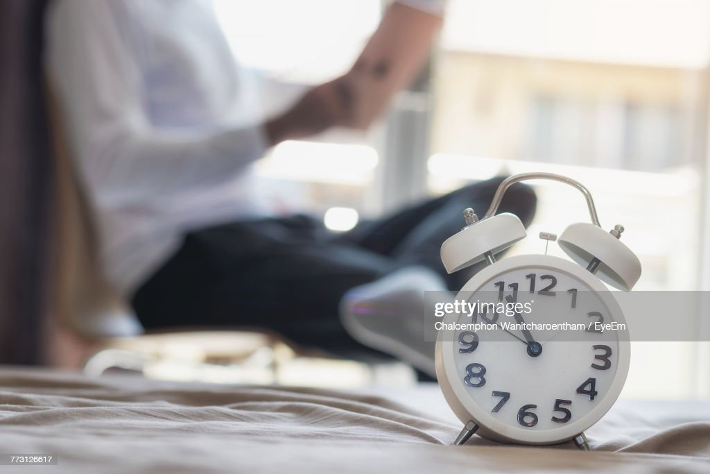 Close-Up Of Alarm Clock With Man Sitting In Background At Home : Stock Photo