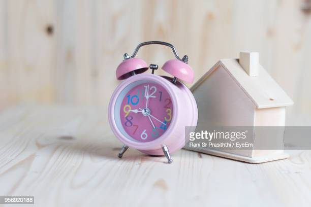close-up of alarm clock with model home on wooden table - cadran d'horloge photos et images de collection
