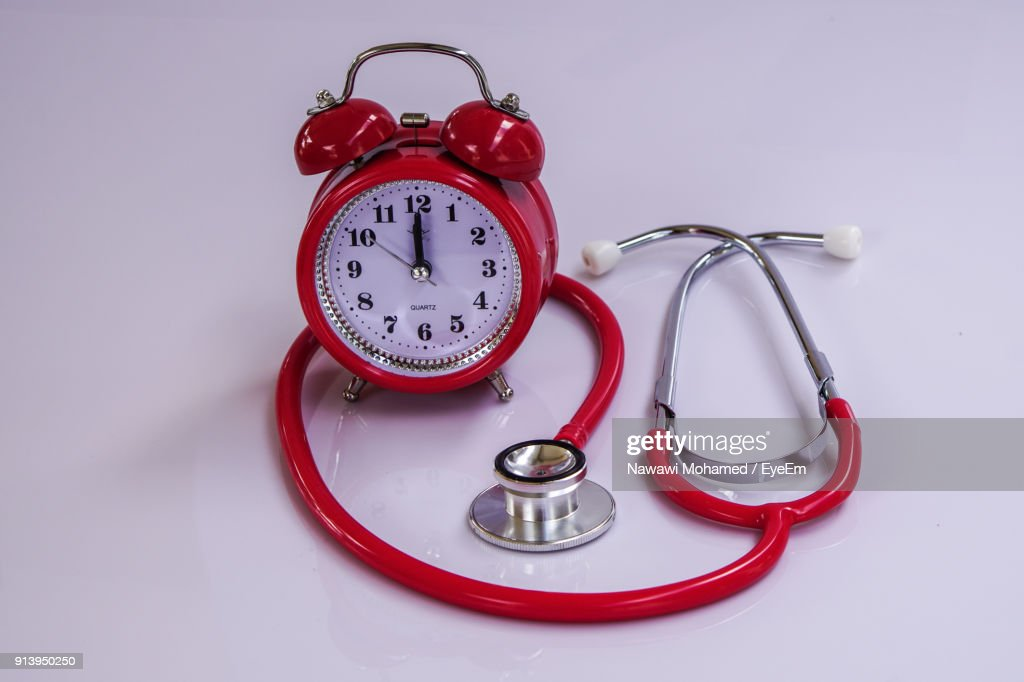 closeup of alarm clock with stethoscope stock photo getty images