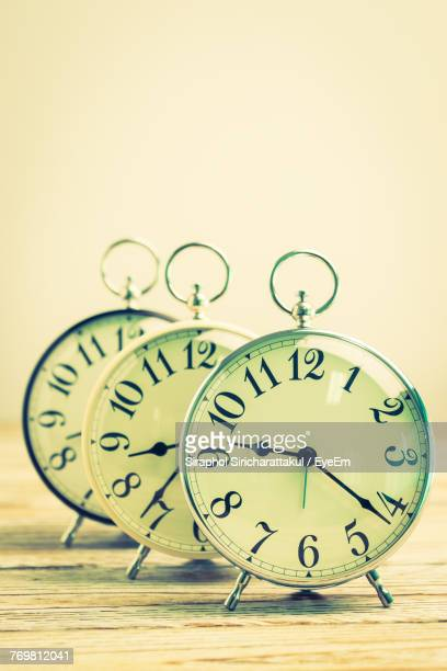 Close-Up Of Alarm Clocks Over White Wall