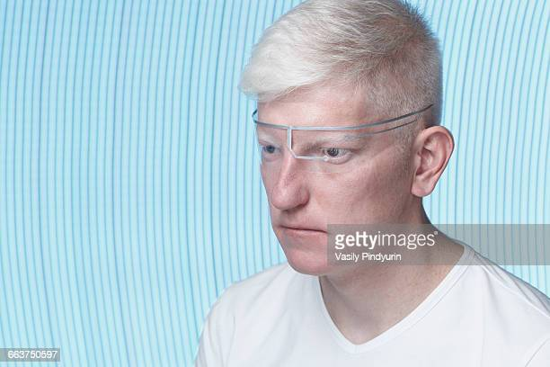 Close-up of albino man wearing protective eyewear against blue background