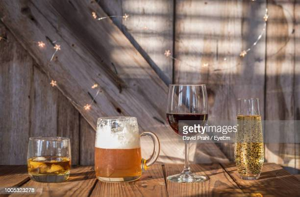 Close-Up Of Alcohol In Various Glasses On Wooden Table