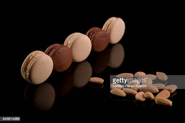 Close-Up Of Almonds And Cookies Over Black Background
