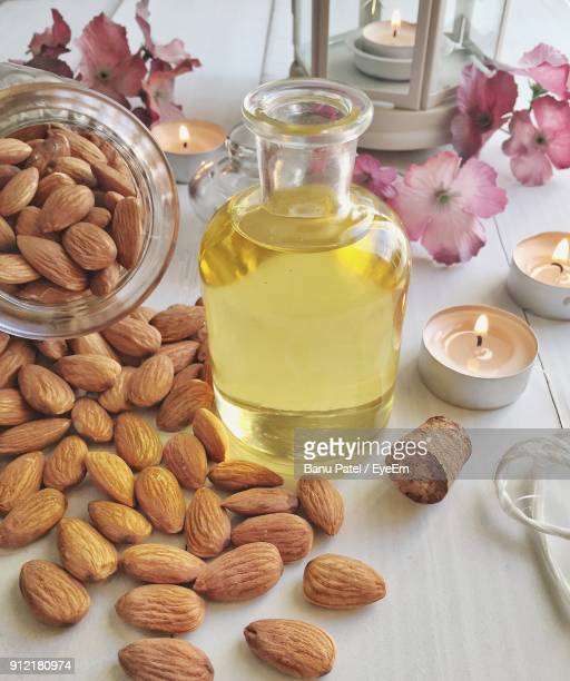 Close-Up Of Almonds And Oil In Bottle On Table