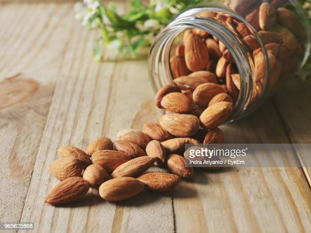 close-up of almonds fallen from glass container on wooden table - almonds stock pictures, royalty-free photos & images