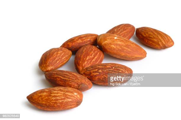 close-up of almonds over white background - almond stock pictures, royalty-free photos & images