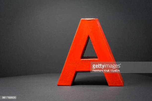 Close-Up Of Alphabet A On Table Against Gray Background