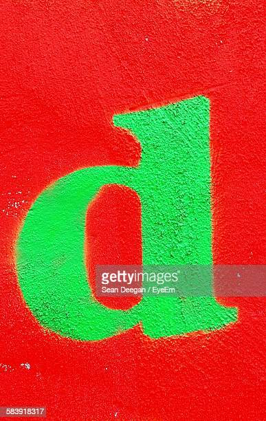 Close-Up Of Alphabet D On Red Wall