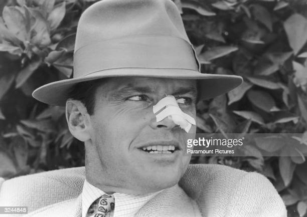 Closeup of American actor Jack Nicholson wearing a fedora and a bandage on his nose in a still from director Roman Polanski's film 'Chinatown'