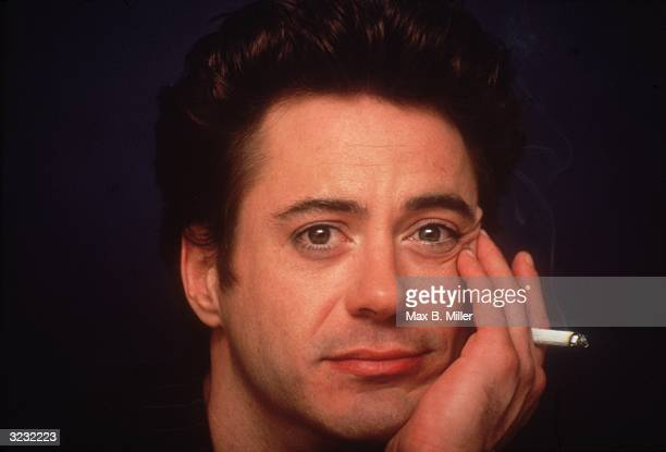 Closeup of American actor Robert Downey Jr holding a cigarette