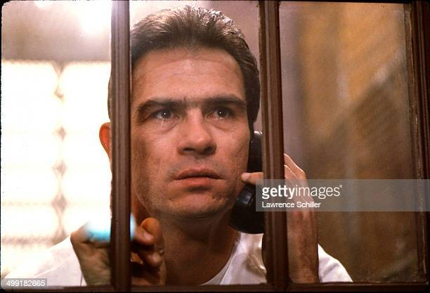 Closeup of American actor Tommy Lee Jones talks on a prison telephone in a scene from the madefortelevision movie 'The Executioner's Song' Provo Utah...