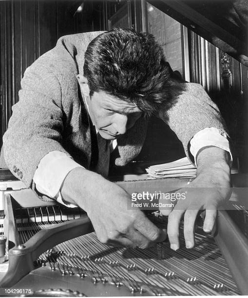 Closeup of American composer John Cage as he tunes a piano April 17 1957