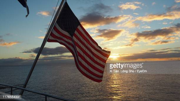 close-up of american flag against sky during sunset - american flag ocean stock pictures, royalty-free photos & images