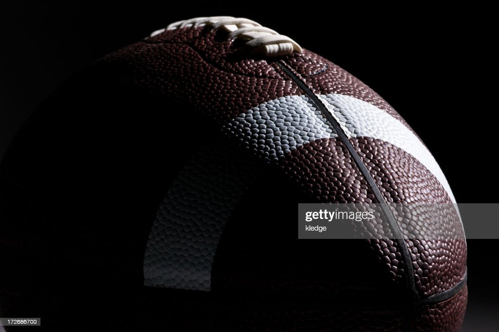 Close-up of American football with dramatic lighting : Bildbanksbilder