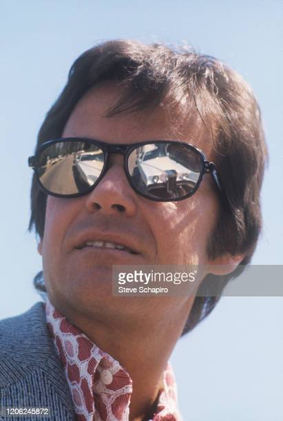 Closeup of American radio and television presenter Dick Clark a white car reflected in his mirrored sunglasses Los Angeles California 1970s