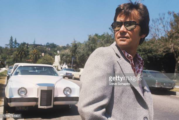 Closeup of American radio and television presenter Dick Clark in mirrored sunglasses as he poses on a street in front of a line of parked cars Los...