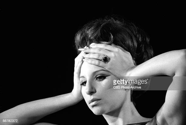 Close-up of American singer and actress Barbra Streisand as she places her hands on her forehead during her live concert in Sheep Meadow, Central...
