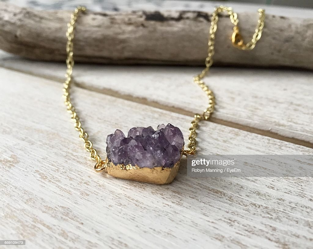 Close-Up Of Amethyst With Gold Necklace On Table : Stock Photo