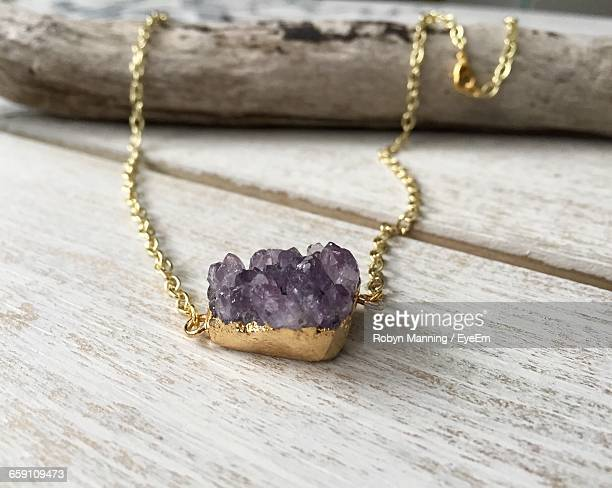 close-up of amethyst with gold necklace on table - amethyst stock pictures, royalty-free photos & images