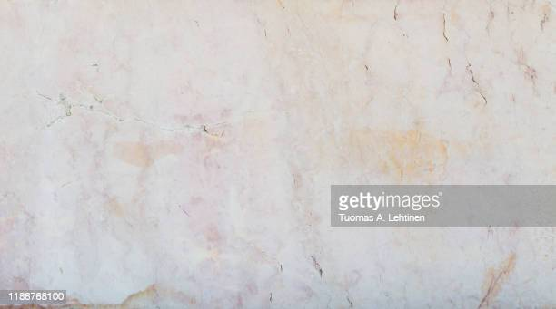 close-up of an aged and cracked smooth natural marble stone wall or flooring. high resolution full frame textured background. - parede imagens e fotografias de stock