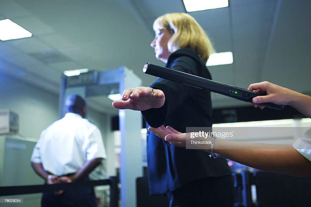 Close-up of an airport security officer using a hand held metal detector to check a traveler : Stock Photo