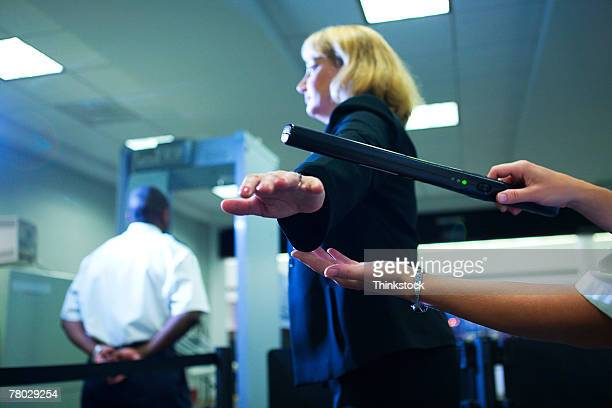 close-up of an airport security officer using a hand held metal detector to check a traveler - security scanner stock pictures, royalty-free photos & images
