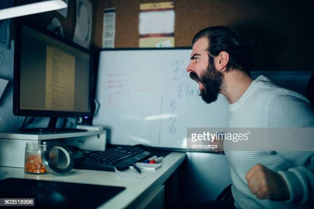 close-up of an angry man working at the home office - fury stock pictures, royalty-free photos & images