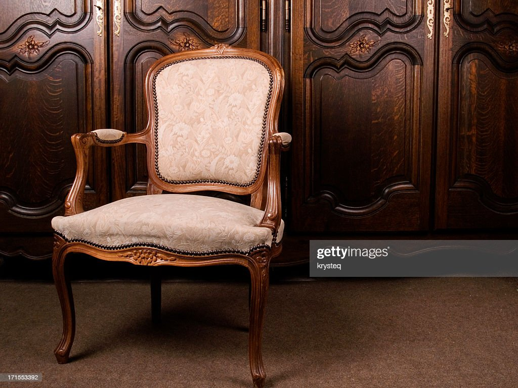 A close-up of an antique cream colored armchair : Stock Photo