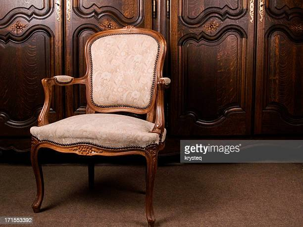 A close-up of an antique cream colored armchair