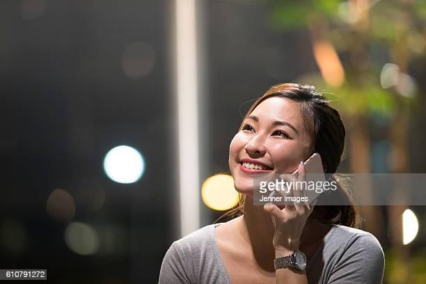 Closeup of an Asian woman talking on a smart phone at night.